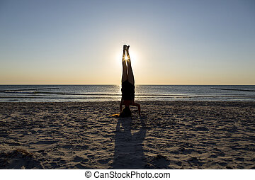 Young woman standing on her hands at the beach.