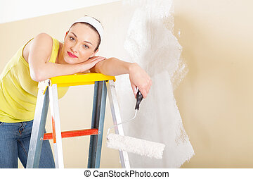 young woman standing on ladder