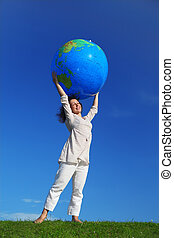 young woman standing on lawn and holding inflatable globe over her head