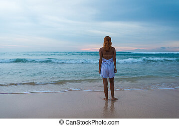 Young woman standing on ocean beach