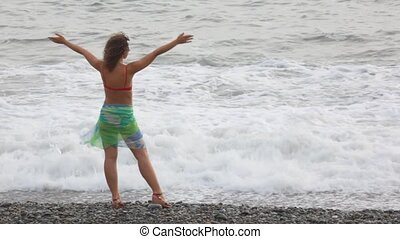 young woman standing on pebble beach against waves of sea