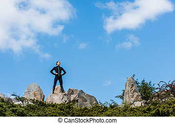 young woman standing on rocks with arms akimbo and looking away