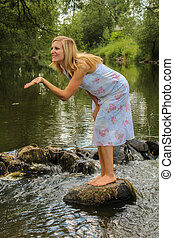 Young woman standing on stone in river, sending kiss