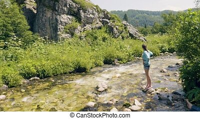 Young woman standing on stone in river water and enjoying on nature landscape