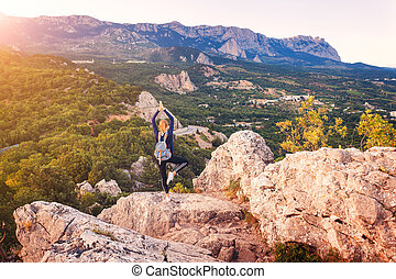 Young woman standing on the mountain peak at sunset