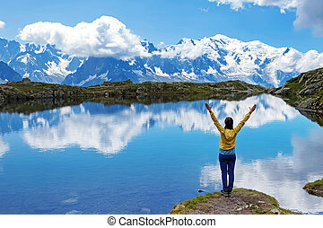 Young woman standing on the shore of scenic mountain lake in Alps with her hands raised.