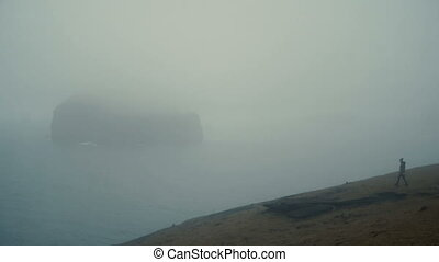 Young woman standing on the shore of the sea in foggy day and enjoying the view in Iceland, thinking about something.