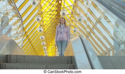 Young woman standing on the top of escalator