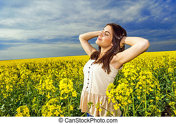 Young woman standing rapeseed - Young woman standing in...