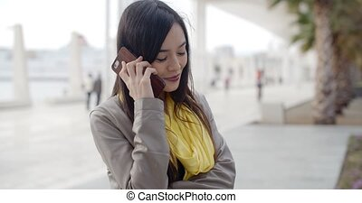 Young woman standing talking on her mobile phone