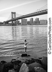 Young woman standing the shore of the East River - Black and...