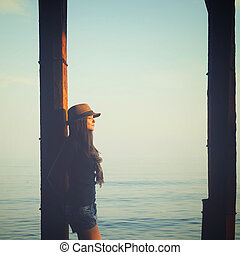 Young woman standing under the pier in a sea water, enjoy autumn sunset light