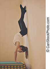 upside down - young woman standing upside down near the wall