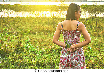 Young woman standing with arms behind her back and hold the tiny flowers in her hand.