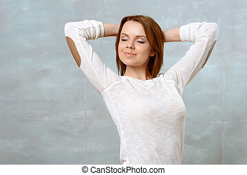 Young woman standing with arms behind her head