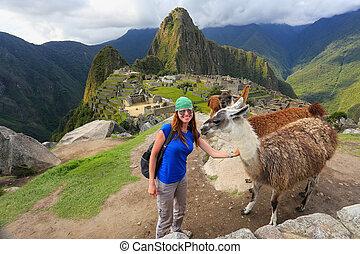 Young woman standing with friendly llamas at Machu Picchu...