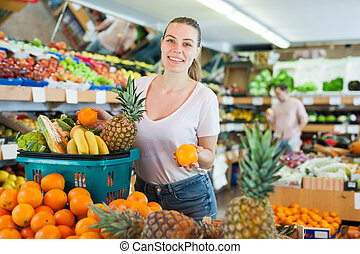 Young woman standing with full grocery cart during shopping