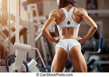 Young woman standing with her back in the gym. Fitness...