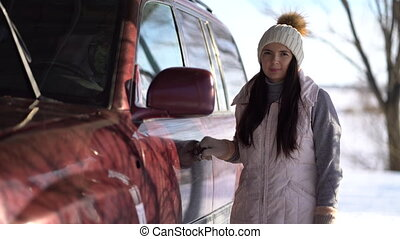 young woman stands near a car in winter.