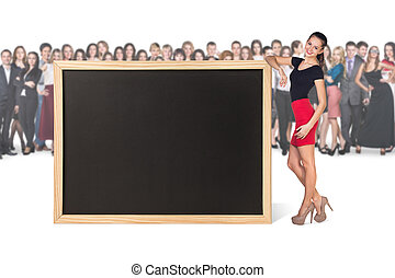 Young woman stands near big chalkboard
