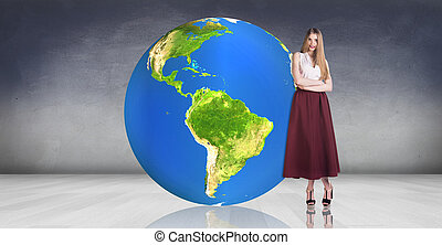 Young woman stands near big earth ball