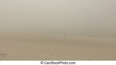 Young Woman Stands on a Yoga Mat, Stretches Out Her Arms in a Misty Weather