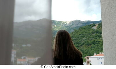 Young woman stands on balcony and looks around green mountains ahead.