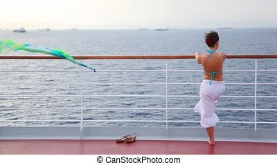 woman stands on deck of cruise liner