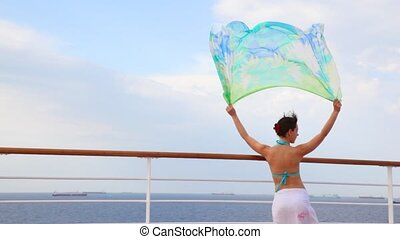 woman stands on deck of ship and holds fabric