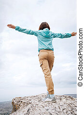 Young woman stands on the top of a mountain.