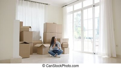 Young woman starting a new life in a new home sitting...