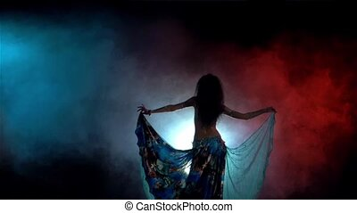 Young woman starting dancing belly dance in blue dress with long dark hair, back light, smoke, slow motion