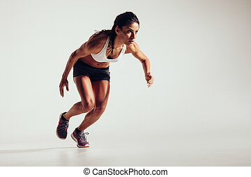 Young woman starting to run and accelerating over grey...