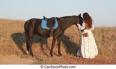Young woman stay near horse on meadow.