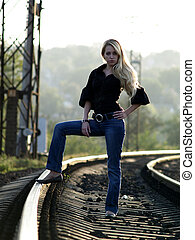 Young blond woman in casual dress staying on railway