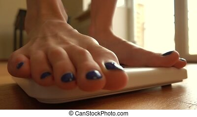 Young woman stepping on the weight scale at home, close-up shot