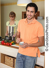 Young woman stirring into saucepan and man holding cup of coffee