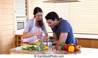 Young woman stirring soup next to her boyfriend