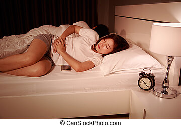 woman stomach pain on bed with her hunsband at night