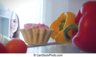 Young woman stops her diet and look for a cake in the refrigerator, but takes vegetable and close The door