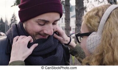 Young woman straightens scarf to her boyfriend
