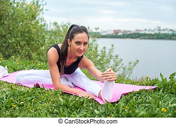 Young woman streching legs street training, fitness, sport