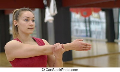 Young woman stretches her arm on fitness in a spacious hall....