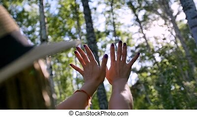 young woman stretches out her hands towards the evening sun ...