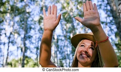 young woman stretches out her hands towards the evening sun in the forest.