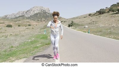 Young woman stretching among mountains - Young fit female in...