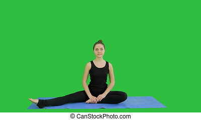 Young woman stretching her legs while doing yoga practice on a Green Screen, Chroma Key