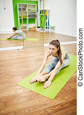 Young Woman Stretching in Fitness Club