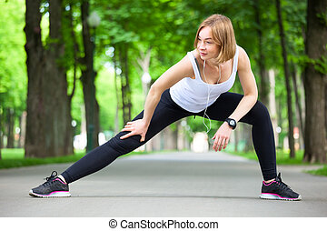 Young woman stretching in the park.