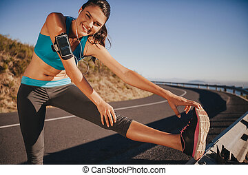 Young woman stretching on guardrail outdoors